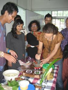 Lawrence having a go at making sambal belacan with the other volunteers waiting their turn.