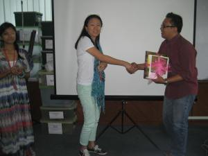 Karen presenting Saiful with a token of appreciation with Mariana looking on.