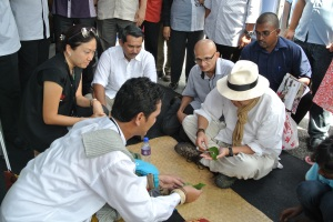Dato' Nazri rolling up a sireh quid with Dato' Ibrahim looking on
